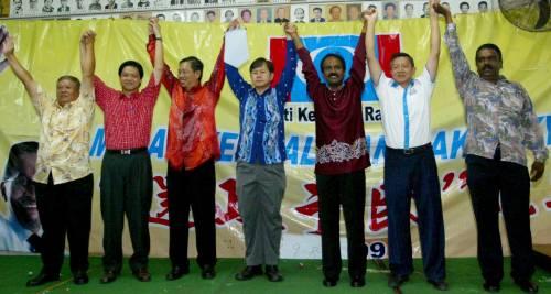 民聯三黨領袖在宴會上高舉起雙手以示團結;左起:公正黨相德花園支部委員張水榮、曾敏凱、尼查、李文材、西華古瑪、劉泉來及西溫。