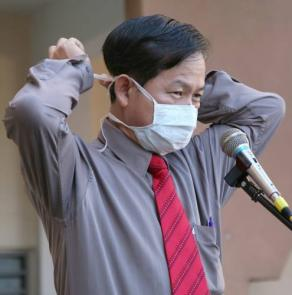 李文材現場示範戴口罩的正確方法。(圖:光明日報)